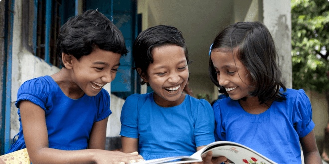 Three girls learning to read in the girls literacy education program